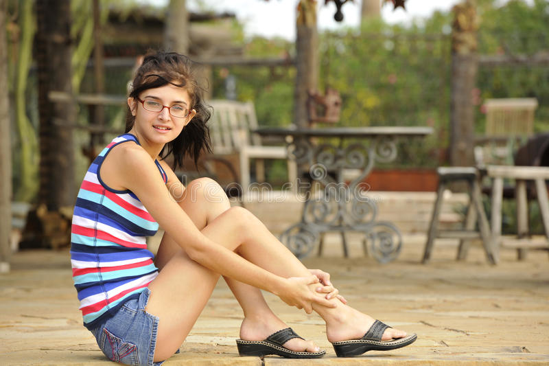 Jeune Brunette s'asseyant sur le patio en pierre images libres de droits
