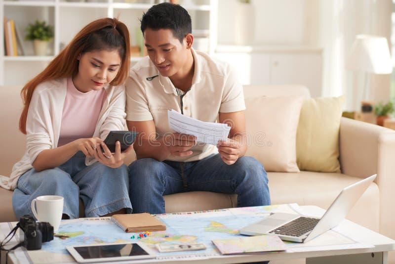 Jeune budget asiatique de vacances de planification de couples photo stock
