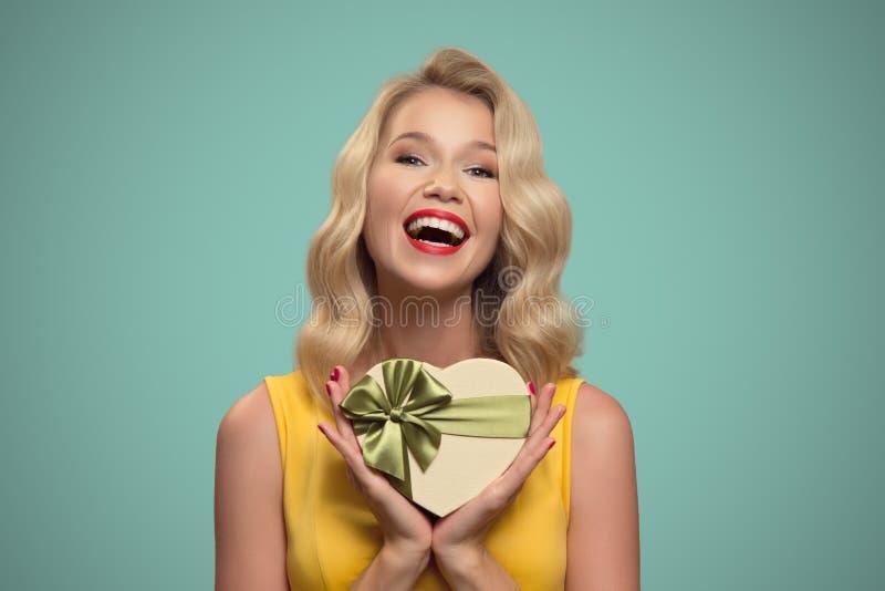 Jeune cadeau de sourire de fixation de femme Jour de Valentine image stock