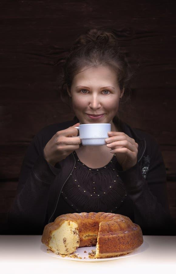 Jeune café potable de sourire de femme et un tarte sur une table photographie stock