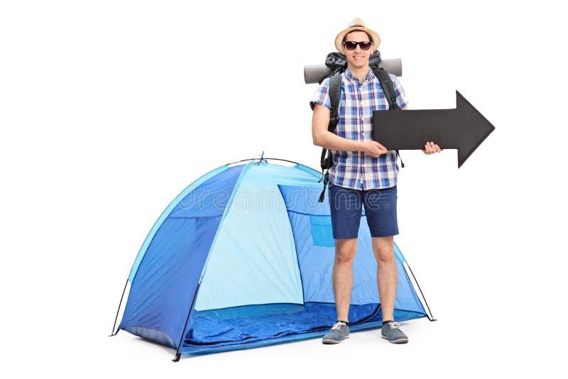 Jeune campeur masculin tenant une flèche photo stock