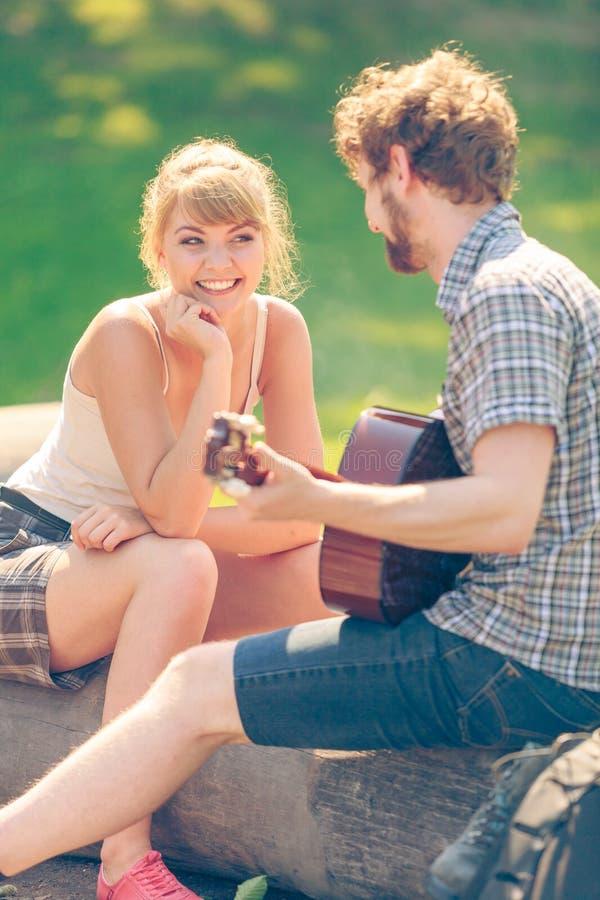 Jeune camping de couples jouant la guitare extérieure photographie stock libre de droits