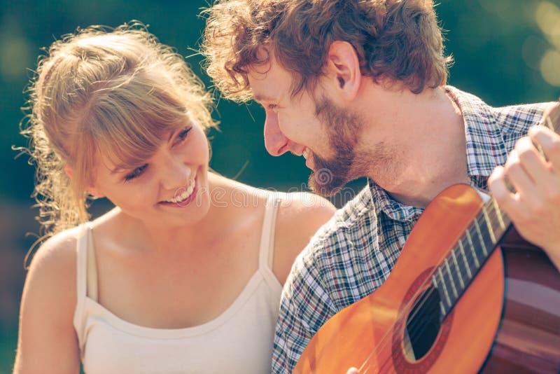 Jeune camping de couples jouant la guitare extérieure photographie stock