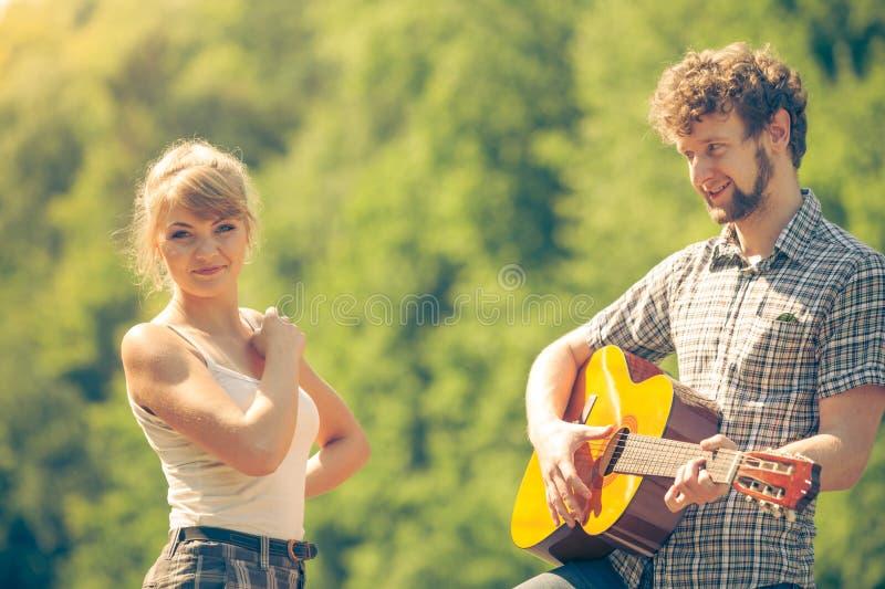 Jeune camping de couples jouant la guitare ext?rieure photographie stock libre de droits