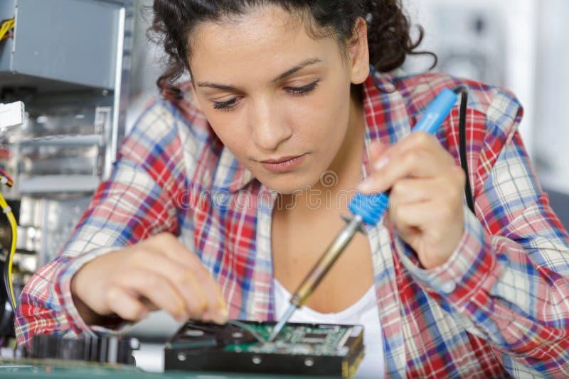 Jeune carte mère de soudure femelle d'ordinateur d'ingénieur électronicien dans le laboratoire photos stock