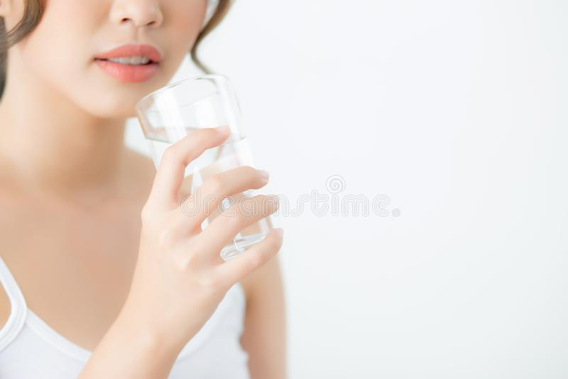 Jeune Caucasien asiatique de femme de beau portrait souriant avec la nutrition assoiff?e et le verre ? boire de minerai de l'eau image libre de droits