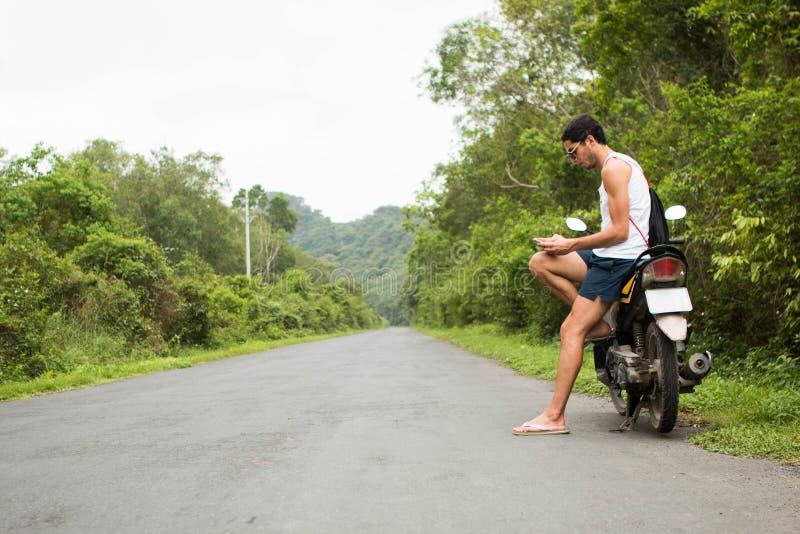 Jeune cavalier de touristes s'asseyant sur une motocyclette de location utilisant un smartphone au milieu d'une route image libre de droits