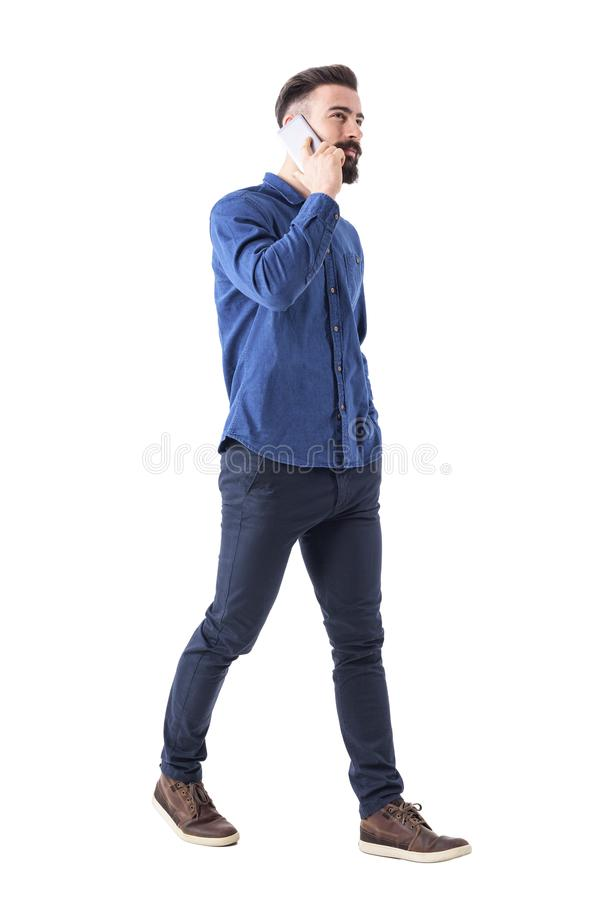 Jeune CEO élégant réussi de mâle marchant et parlant au téléphone portable recherchant images stock