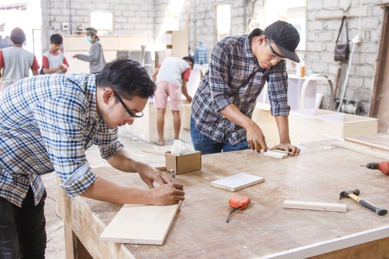 Jeune charpentier mesurant et marquant le conseil en bois photo libre de droits