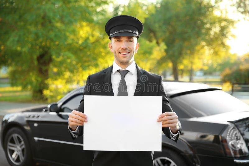 Jeune chauffeur se tenant avec le conseil blanc près de la voiture de luxe images stock