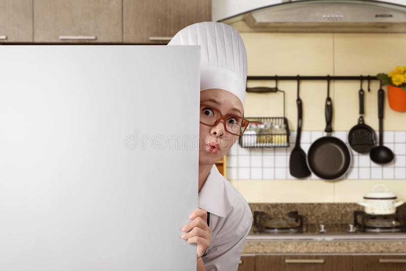 Jeune chef asiatique de femme se tenant par derrière le conseil blanc image stock