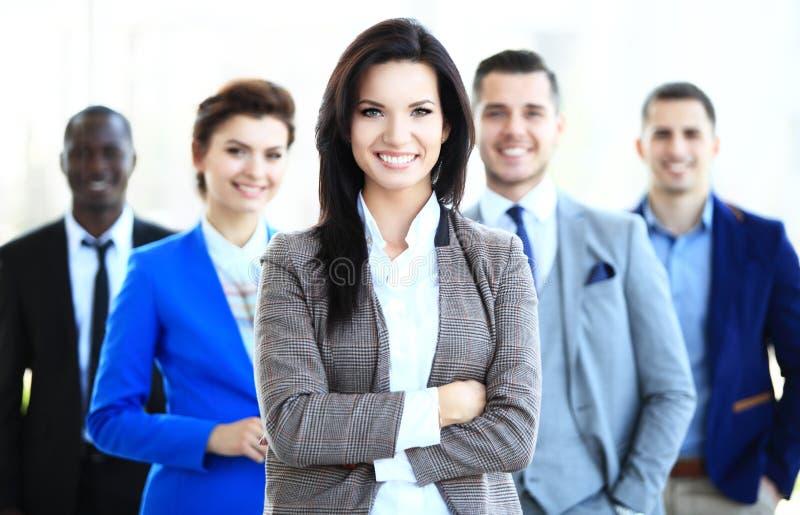 Jeune chef de file des affaires féminin heureux se tenant devant son équipe photo stock
