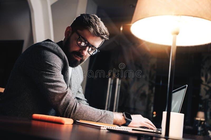 Jeune chef de projet regardant sur le bloc-notes de papier et le texte de dactylographie sur l'ordinateur portable contemporain images libres de droits