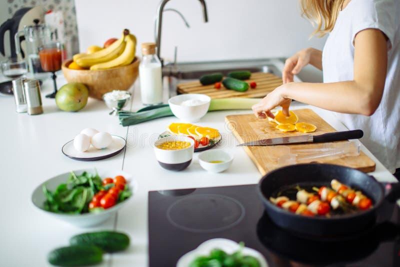 Jeune chef féminin faisant cuire dans la cuisine photos stock