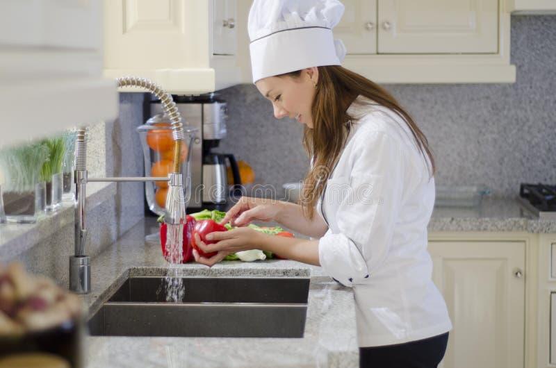 Jeune chef lavant quelques légumes images stock
