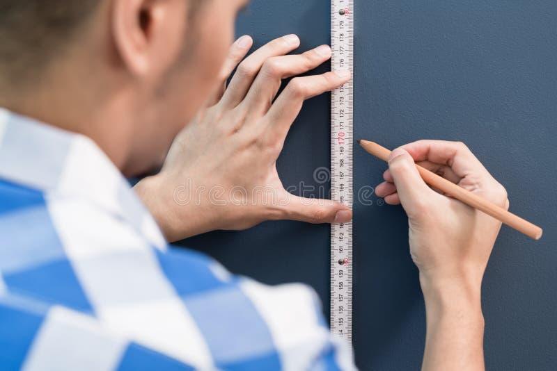 Jeune classement par taille de bricoleur avec le critère et le crayon images stock
