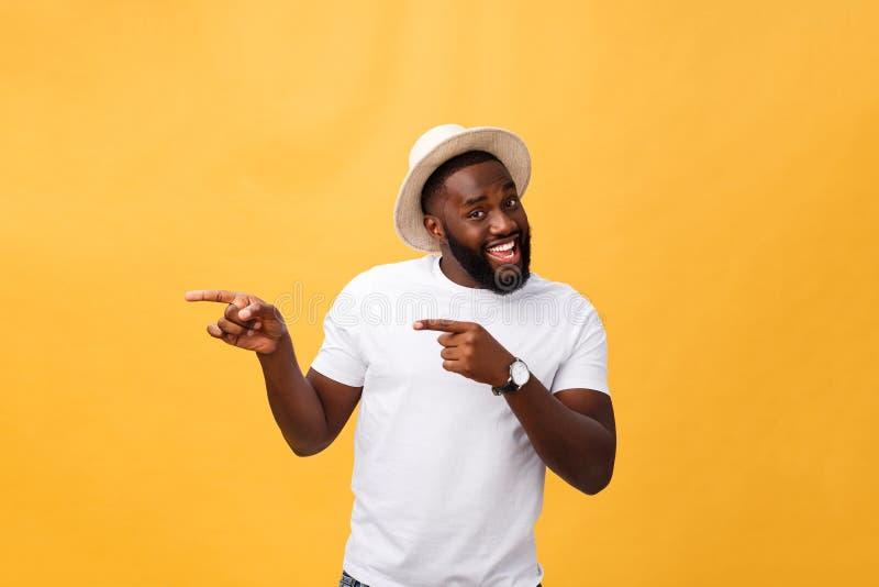 Jeune client africain drôle souriant heureusement et indiquant ses index à la caméra comme si vous choisissant et l'invitant images libres de droits