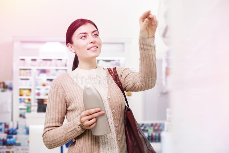 Jeune client curieux choisissant des produits de soin personnel photos stock