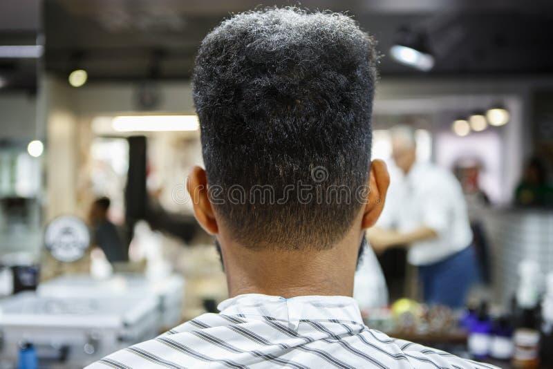 Jeune client d'homme de couleur obtenir la nouvelle coupe de cheveux dans le raseur-coiffeur image stock