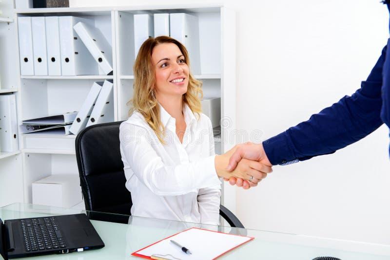 Jeune client de salutation de femme d'affaires avec la poignée de main photos stock