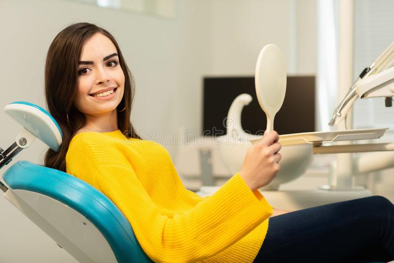Jeune client heureux de femme regardant le miroir avec le sourire toothy le bureau dentaire photos stock