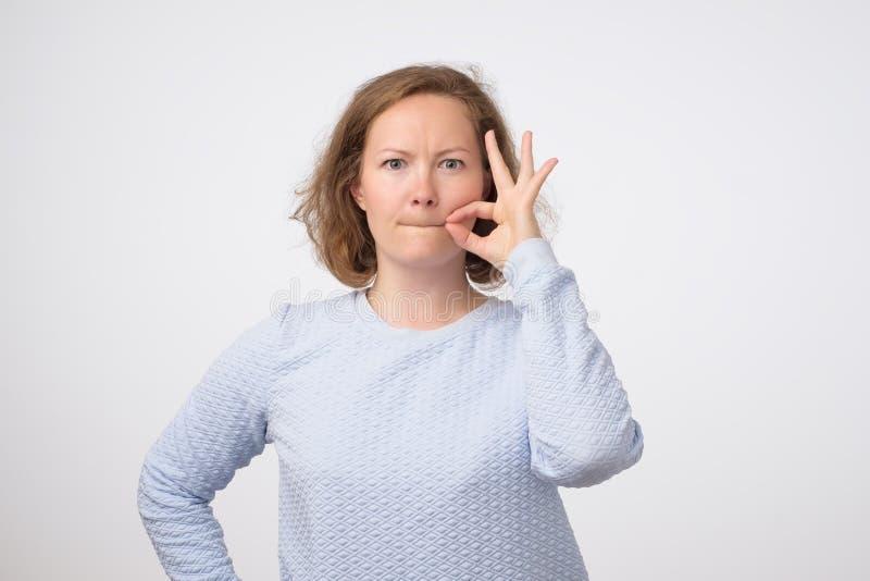 Jeune closinge européen de femme que sa bouche aiment sur la tirette sur le fond gris images libres de droits