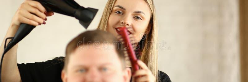 Jeune coiffeur Drying Male Hair par le dessiccateur de coup images stock
