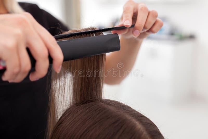 Jeune coiffeur gai en faisant les cheveux femelles image libre de droits
