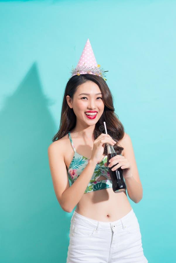 Jeune coke heureux de boissons de fille de bouteille au-dessus de dos coloré de bleu images libres de droits