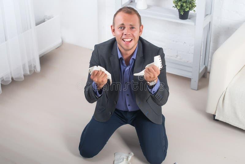 Jeune colère masculine d'homme d'affaires, agenouillement hysterique sur le plancher, cris et tenir le papier chiffonné dans des  photo libre de droits