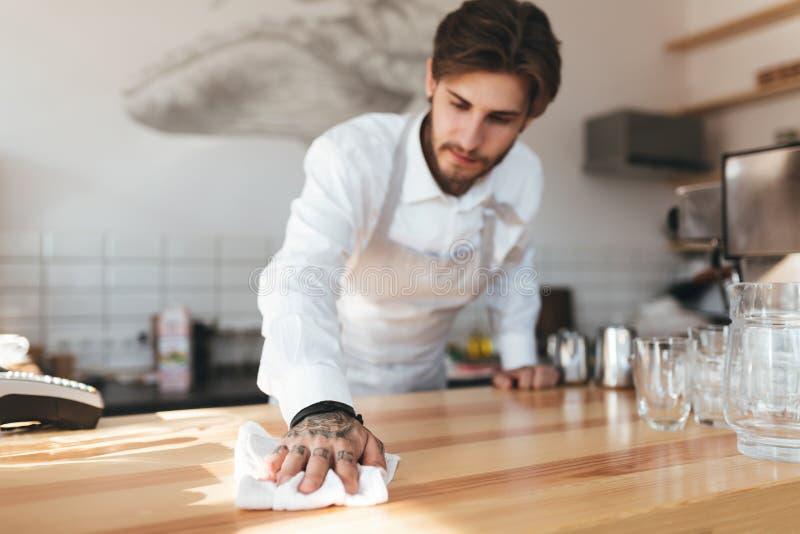 Jeune compteur de nettoyage de barman fonctionnant au café image libre de droits