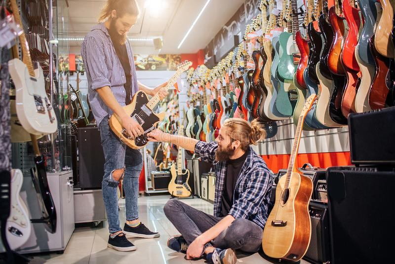 Jeune concentratedc heureux de hippies sur une guitare électrique Premier le tiennent et regardent vers le bas Second se reposent image libre de droits