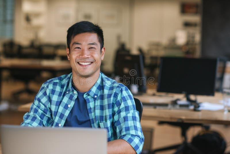 Jeune concepteur asiatique de sourire à l'aide d'un ordinateur portable à son bureau photo libre de droits