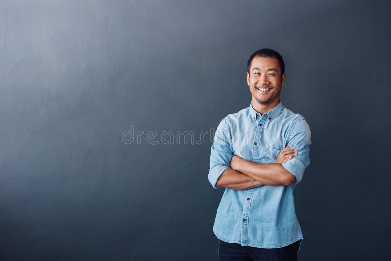 Jeune concepteur asiatique sûr se tenant dans un bureau moderne image stock