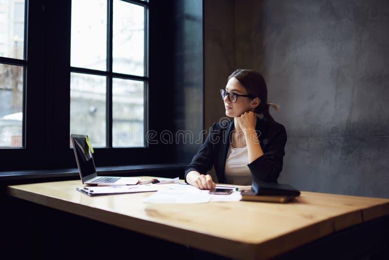 Jeune concepteur féminin attirant songeur s'asseyant à la table image libre de droits