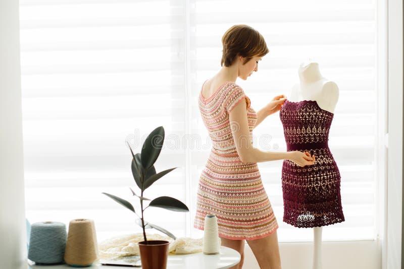 Jeune concepteur féminin aux cheveux courts employant le simulacre de robe au mode de vie intérieur et indépendant à la maison co images stock