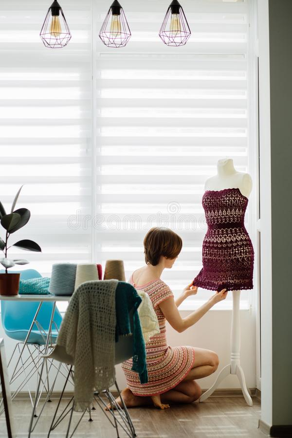 Jeune concepteur féminin d'habillement employant le simulacre de robe au mode de vie intérieur et indépendant à la maison confort images stock