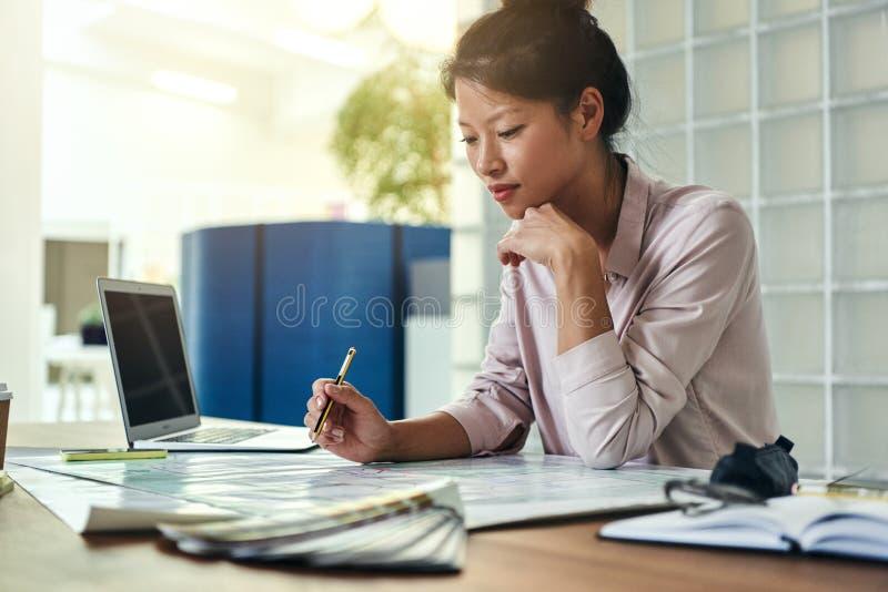 Jeune concepteur féminin regardant au-dessus des plans de bâtiment dans un bureau photo libre de droits