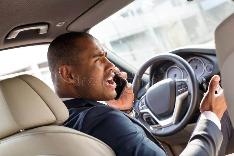 Jeune conducteur d'homme d'affaires conduisant la vue fâchée de réponse de siège arrière d'appel téléphonique de voiture image stock