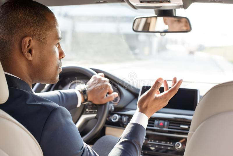 Jeune conducteur d'homme d'affaires s'asseyant à l'intérieur de la voiture regardant de côté la vue arrière concernée par véhicul photographie stock