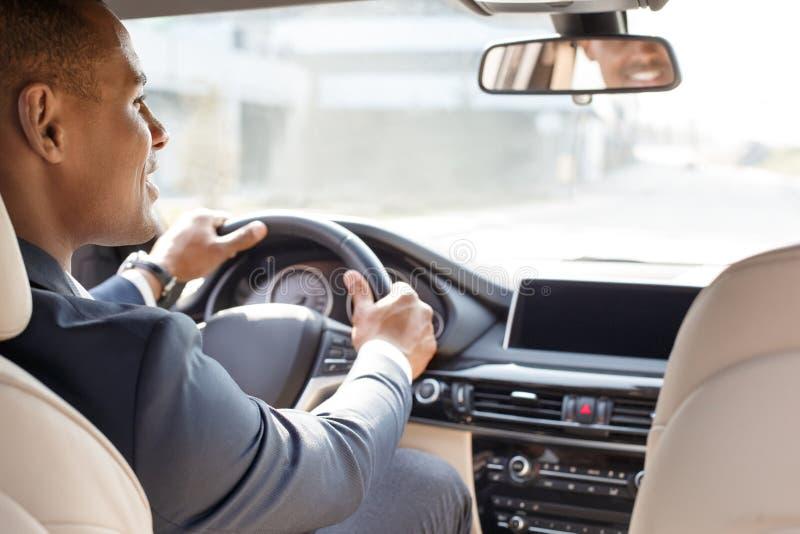 Jeune conducteur d'homme d'affaires s'asseyant à l'intérieur de la voiture regardant de côté la vue gaie de siège arrière photos libres de droits