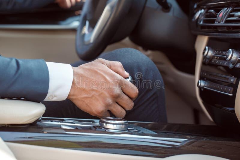 Jeune conducteur d'homme d'affaires s'asseyant à l'intérieur du plan rapproché d'embrayage de vitesse de participation de voiture images libres de droits
