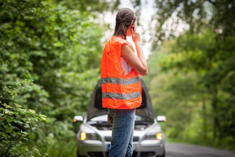 Jeune conducteur féminin appelle le service de bord de la route photo libre de droits