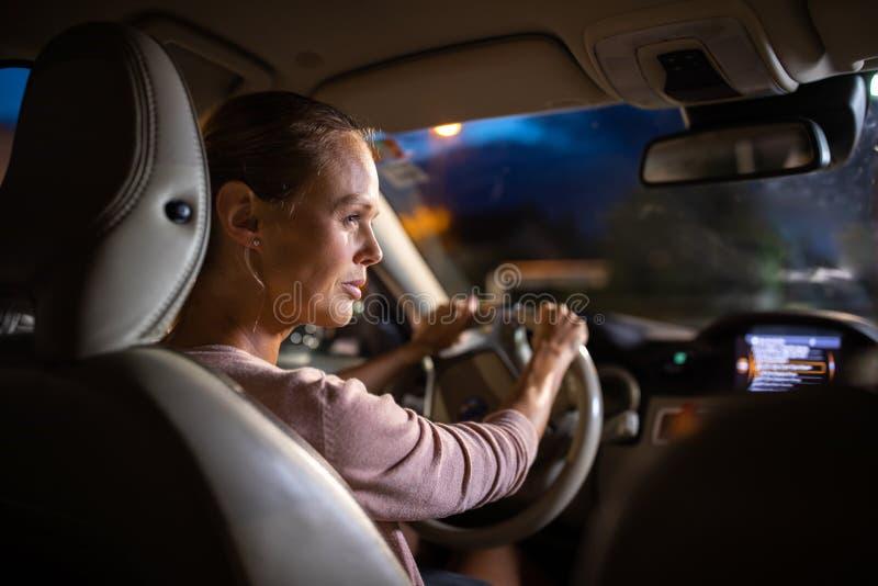 Jeune conducteur femelle conduisant sa voiture la nuit images stock