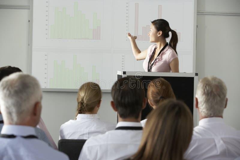 Jeune conférence de Delivering Presentation At de femme d'affaires image stock