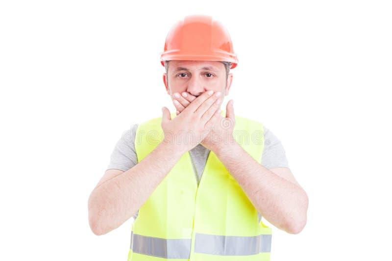 Jeune constructeur couvrant sa bouche comme concept de silence photographie stock libre de droits
