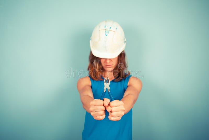 Jeune constructeur femelle tenant des pinces photos libres de droits