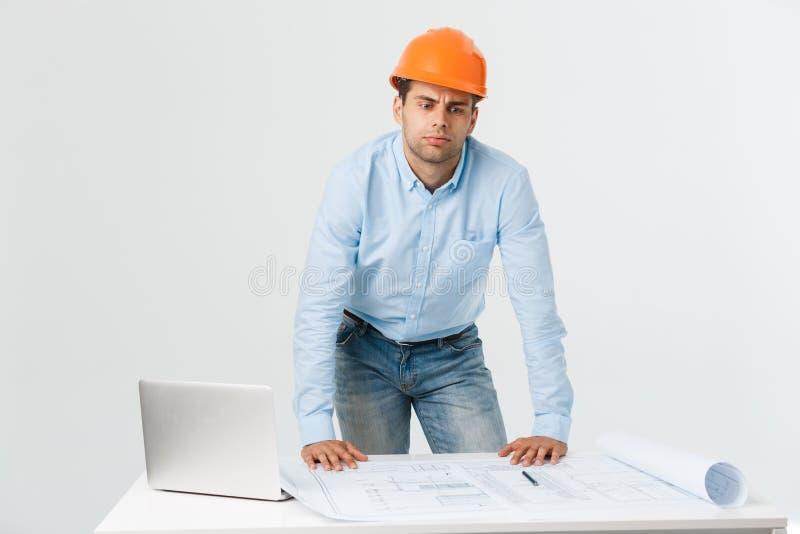 Jeune constructeur soumis à une contrainte ayant le mal de tête ou la migraine semblant épuisée et inquiétée sur le fond blanc av photos libres de droits