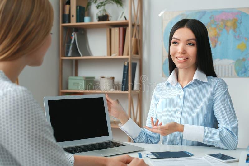 Jeune consultant en matière féminin d'agent de voyage à l'agence de visite avec un présent de client une visite sur un ordinateur photographie stock