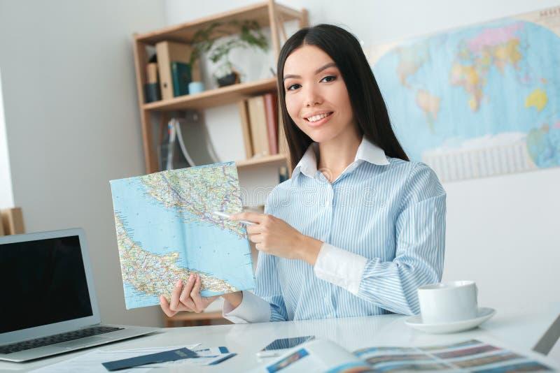 Jeune consultant en matière féminin d'agent de voyage à l'agence de visite tenant la carte image stock